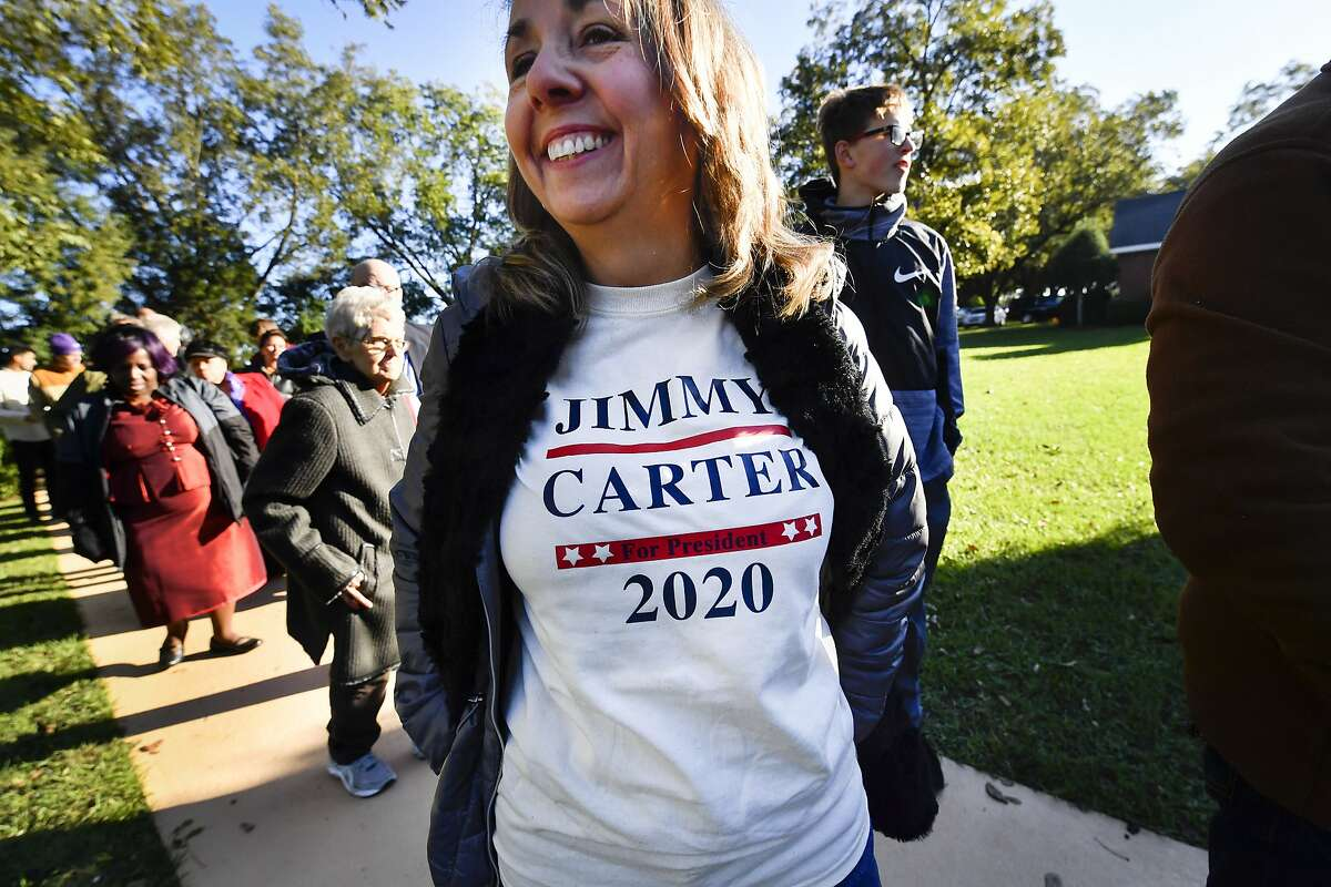 In this Sunday, Nov. 3, 2019, photo, Tammy Bailey wears a message on her shirt as she waits in line to attend former President Jimmy Carter's Sunday school class at Maranatha Baptist Church, in Plains, Ga. (AP Photo/John Amis)