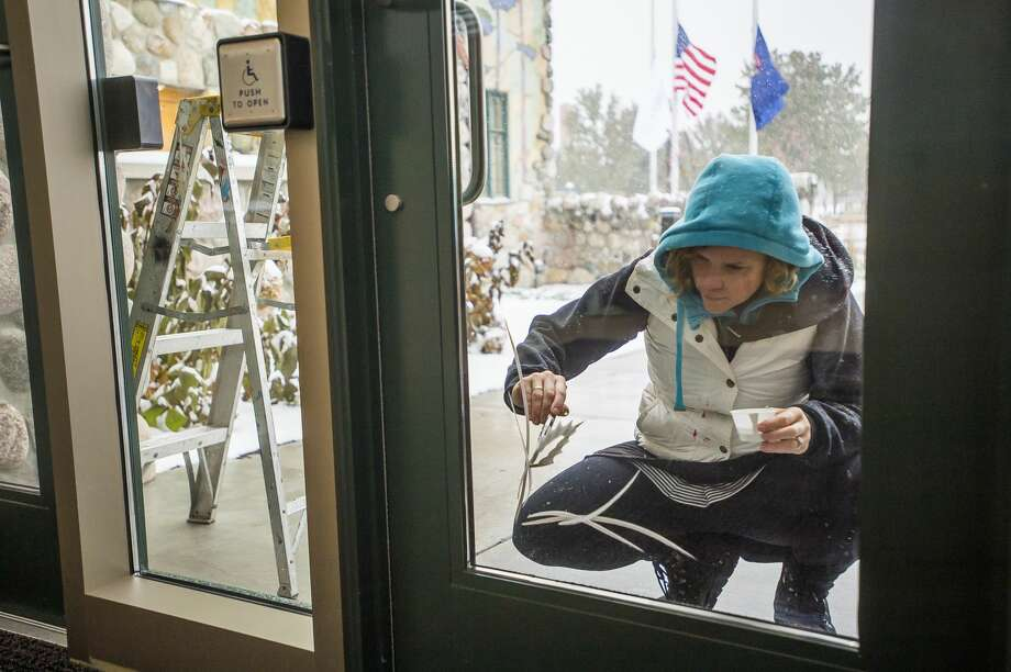 Mary Thiefels of the Brush Monkeys painting group adds a winter scene to a window at the Midland County Courthouse Monday, Nov. 11, 2019. (Katy Kildee/kkildee@mdn.net) Photo: (Katy Kildee/kkildee@mdn.net)