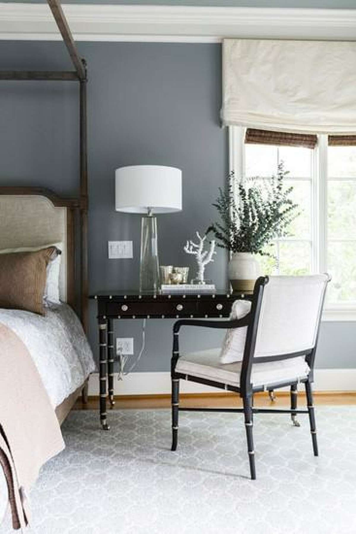 A small writing desk doubles as a nightstand in this bedroom.