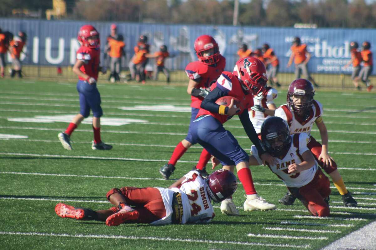 La Porte Texans ballcarrier Anthony Rojas, who almost single-handedly ruined the Rams chances of winning the Junior Super Bowl, has  Sean Simon (24) and two other Rams slowing him down during second-half action Saturday.