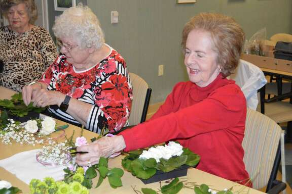 Carla Gaut, The Buckingham senior living community resident and certified flower judge, shows other residents how to make floral arrangements on Thursday, Nov. 7, for memory care residents. November is Alzheimer's Awareness Month, and 1.76 million Texans battle the debilitating disease.