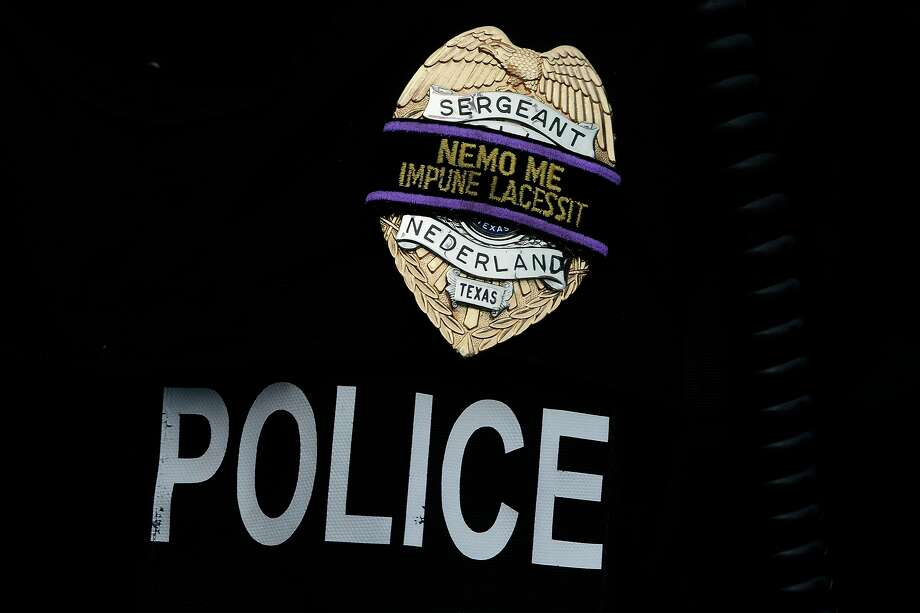 "Nederland police Sgt. David Odom wears a black band over his badge during a vigil Friday evening at the Nederland Police Department for law enforcement officers killed in Dallas on Thursday night. The Latin phrase on the band translates to ""no one cuts me with impunity.""  Photo taken Friday 7/8/16 Ryan Pelham/The Enterprise Photo: Ryan Pelham / Ryan Pelham/Ryan Pelham/The Enterprise / ©2016 The Beaumont Enterprise/Ryan Pelham"