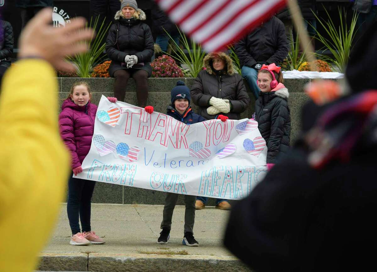 Kara Kaminski, 10, left, of Colonie, Brian Cummings, 8, center, of Colonie, and Brian's sister, Meghan Cummings, 12, hold a sign to thank and honor veterans as they watch the Albany Veterans Day Parade on Monday, Nov. 11, 2019, in Albany, N.Y. (Paul Buckowski/Times Union)