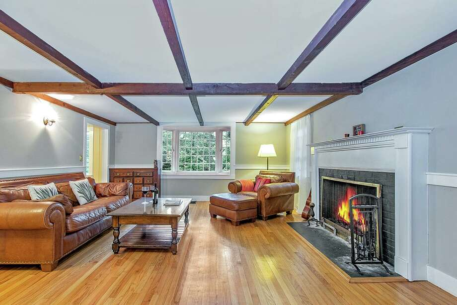 The sizable living room features thick chair railing, a bay window, a ceiling of exposed beams, and a fireplace.