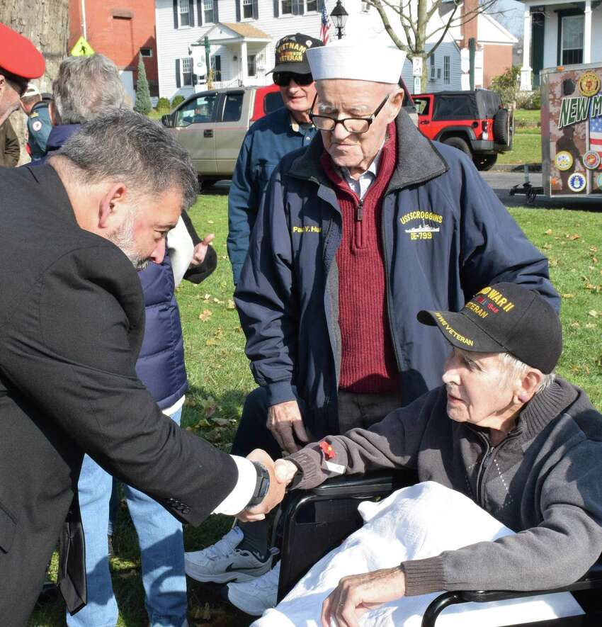 Spectrum/The annual Veterans Day ceremony was held on the south end of the Village Green in New Milford Nov. 11, 2019. Above, New Milford Mayor Pete Bass thanks veterans Paul Hulton, standing, and Ed Tierney for their service to our country following the ceremony.