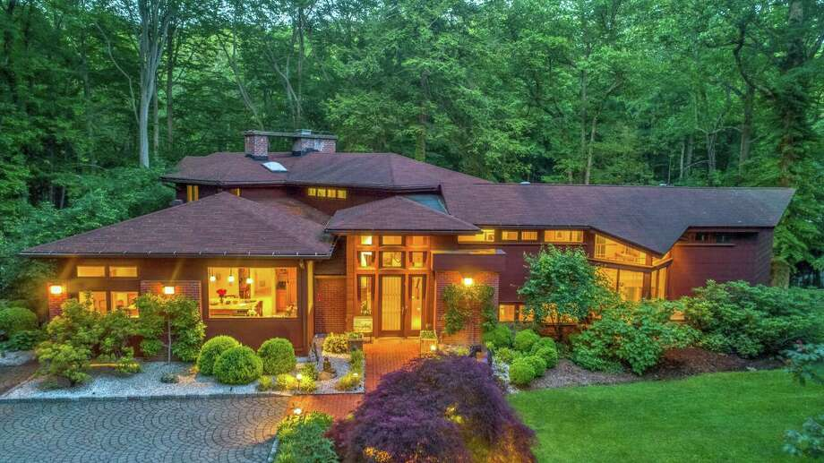 "The property named ""Rivers Edge"" with a brown-colored contemporary house at 19 Hemlock Ridge Road, was inspired by iconic architect Frank Lloyd Wright."