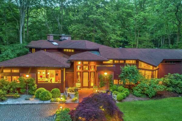 """The property named """"Rivers Edge"""" with a brown-colored contemporary house at 19 Hemlock Ridge Road, was inspired by iconic architect Frank Lloyd Wright."""