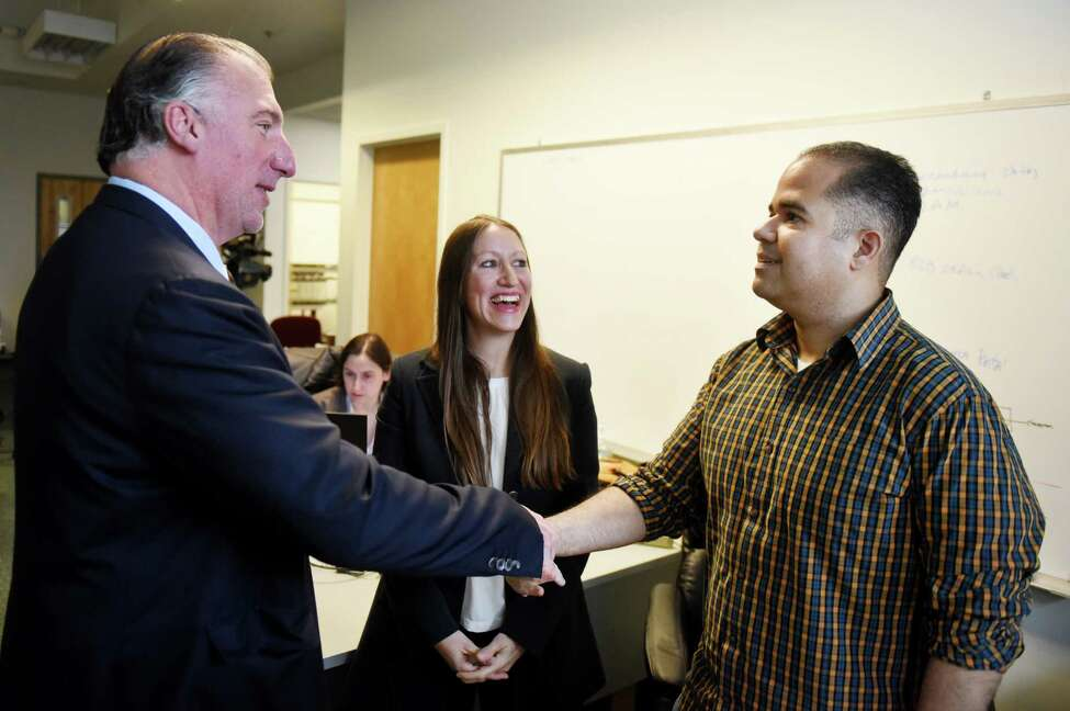 SEFCU CEO Michael Castellana, left, and AlbanyCanCode founder and CEO Annmarie Lanesey, center, talk with Air Force veteran and software programmer Ramon Vazquez, right, on Monday, Nov. 11, 2019, at the UPPmarket office in Troy, N.Y. Vazquez learned computer programming after taking classes through AlbanyCanCode, a Troy nonprofit group that organizes computer programming classes at local community colleges. (Will Waldron/Times Union) Annmarie Lanesey