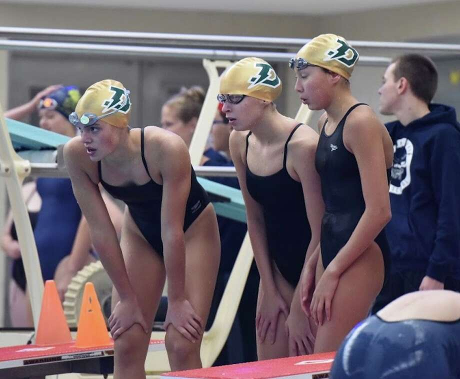 From left, Dow High's Claire Newman, Sasha Konovalenko and Ella Roberson cheer on teammate Anna Jensen during the 200-yard freestyle in Saturday's SVL swim championships at Saginaw Valley State University. Dow won the event with a meet-record and school-record time of 1 minute, 38.14 seconds. Photo: Photo Provided