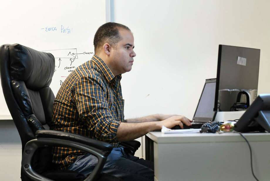 Air Force veteran Ramon Vazquez writes Javascript programming for UPPmarket on Monday, Nov. 11, 2019, at their Frear Building office in Troy, N.Y. Vazquez learned computer programming after taking classes through AlbanyCanCode, a Troy nonprofit group that organizes computer programming classes at local community colleges. (Will Waldron/Times Union) Photo: Will Waldron, Albany Times Union / 40048229A