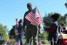 Conroe resident and Vietnam War Veteran Henry Calyen, 69, smiles as his great grandson, Anthony Howard, 5 of Montgomery, helps place over 600 flags with the Montgomery County Veterans Memorial Commission at Veterans Memorial Park in Conroe on Saturday, November 9, 2019.