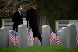 Democratic presidential hopeful Mayor Pete Buttigieg (L) walks through the New Hampshire State Veterans Cemetery in Boscawen, New Hampshire, on November 11, 2019, with fellow veteran Thomas Gary, a senior petty officer at Naval Station Great Lakes, for a Veterans Day service as he continues his 4-day bus tour of the state. - Pete Buttigieg is criss-crossing New Hampshire on a mission: to convince voters that a 30-something smalltown mayor with an unapologetically moderate message is the Democratic Party's best shot at ousting President Donald Trump. (Photo by JIM WATSON / AFP) (Photo by JIM WATSON/AFP via Getty Images)