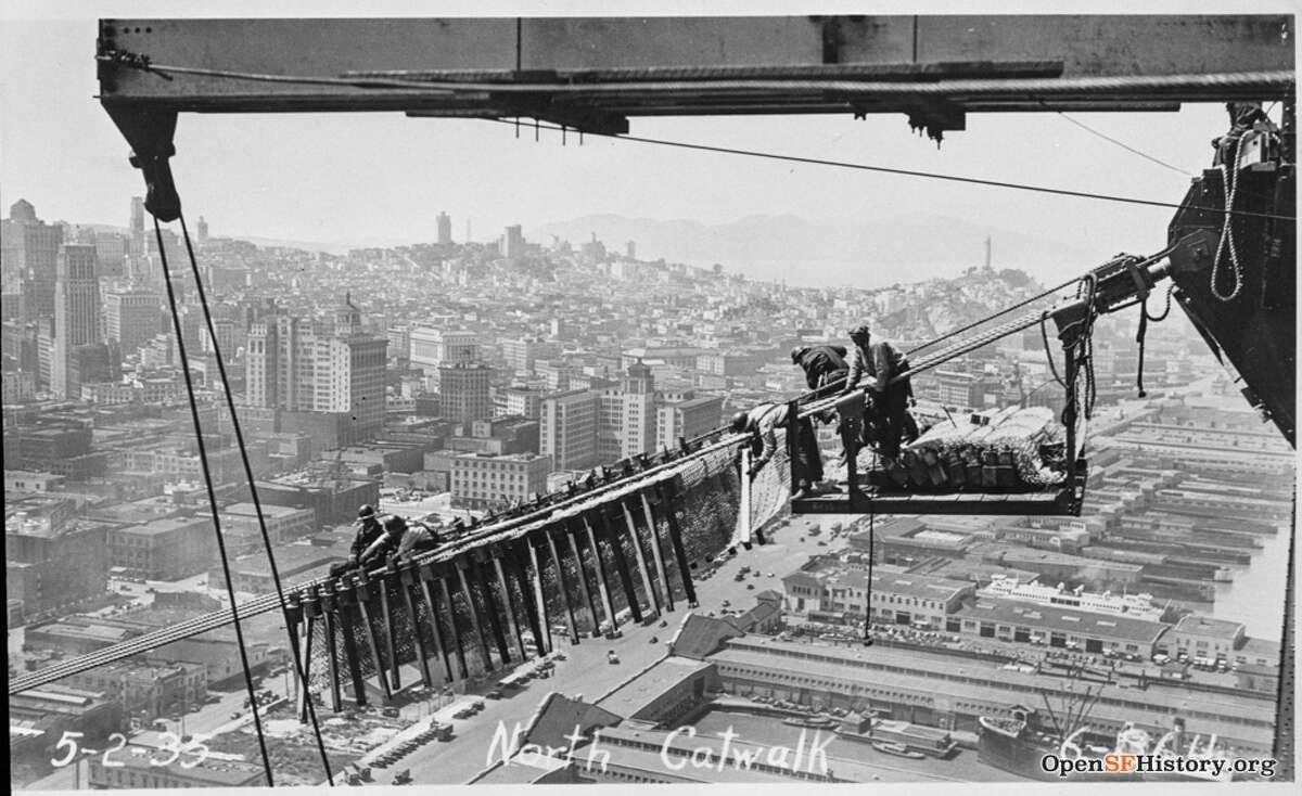 Bat Bridge construction workers on a catwalk above San Francisco circa 1935.