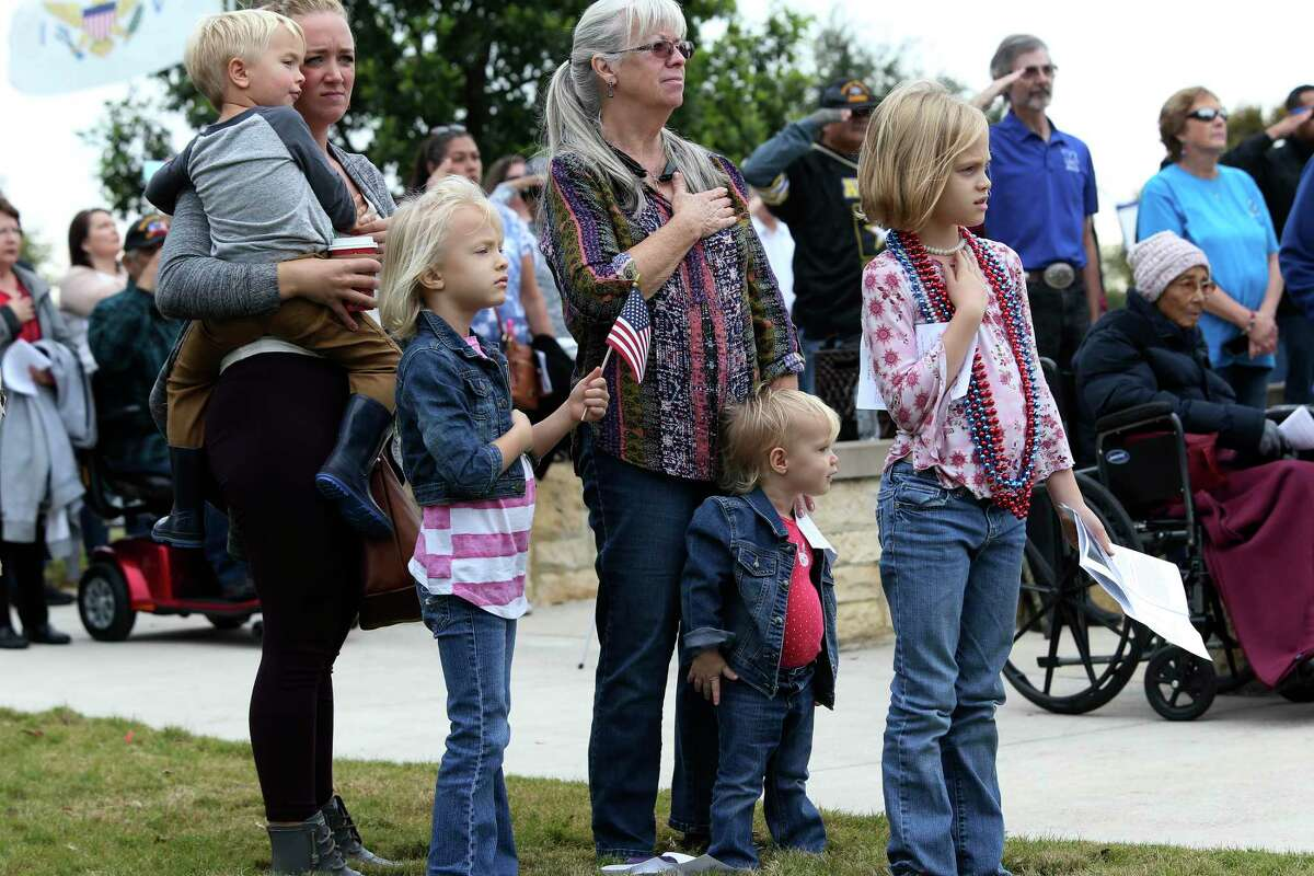 Brooke Fowl, 27, left, holding her son, Shepherd, 3, and her mother-in-law, Kathleen Fowl, 63, attend the Veterans Day ceremony at Fort Sam Houston National Cemetery on Monday. With them are Shepherd's cousins, from left, Meg Fowl, 5, Kate Fowl, 2, and Fiona Fowl, 7. The ceremony honored military veterans and families.