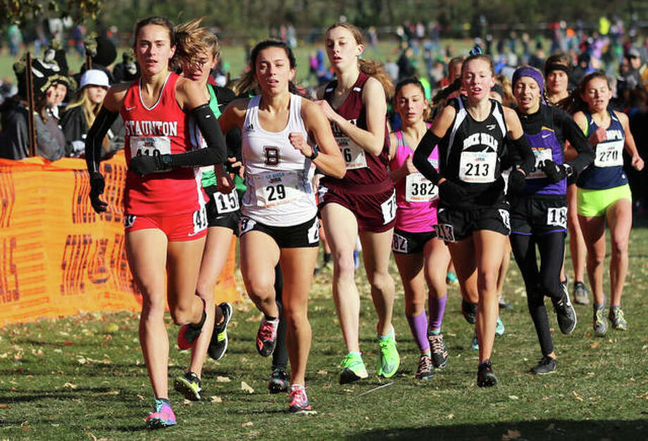 Staunton's Lydia Roller (left) and Benton's Amelia McLain (29) lead the field behind front-running Lianna Surtz of Aurory Rosary in the opening mile of the Class 1A girls cross country state meet Saturday morning at Detweiller Park. Surtz won the race, with Roller finishing second and McLain taking third. Photo: Greg Shashack / The Telegraph