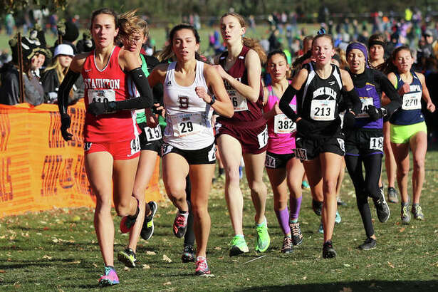 Staunton's Lydia Roller (left) and Benton's Amelia McLain (29) lead the field behind front-running Lianna Surtz of Aurory Rosary in the opening mile of the Class 1A girls cross country state meet Saturday morning at Detweiller Park. Surtz won the race, with Roller finishing second and McLain taking third.