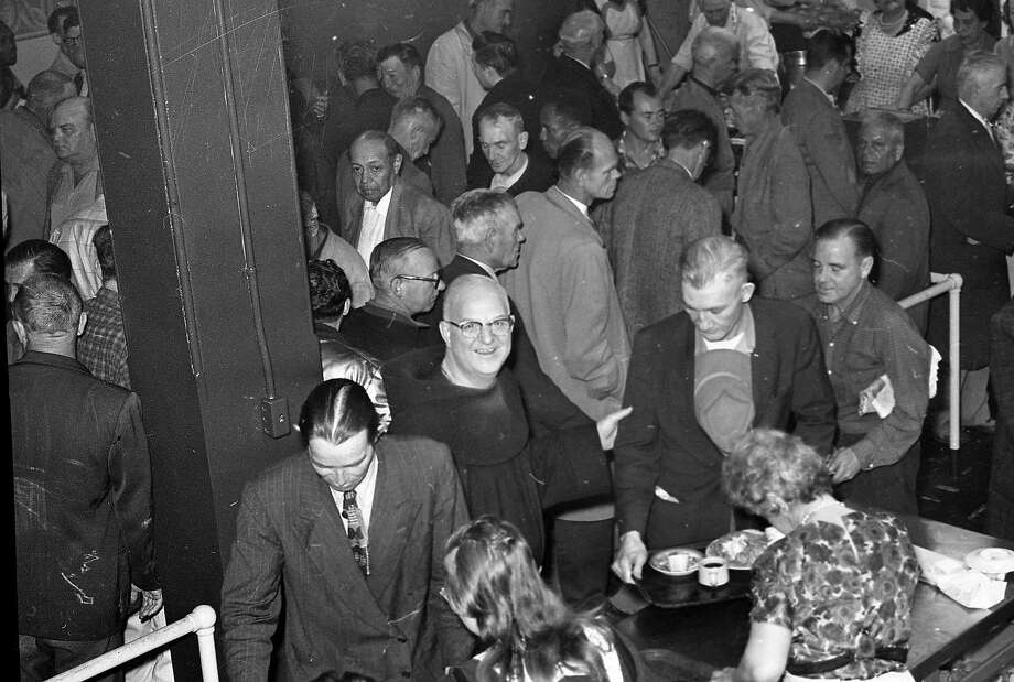 The line moves steadily at St. Anthony Dining Room's Thanksgiving dinner on Nov, 23, 1961, with the Rev. Alfred Boeddeker at center. Photo: Joe Rosenthal / The Chronicle 1961