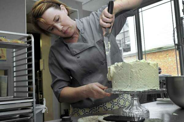 Anna Llanos, owner of Mothership on Main, frosts a chocolate cake with espresso whipped creme, Thursday, July 27, 2017.
