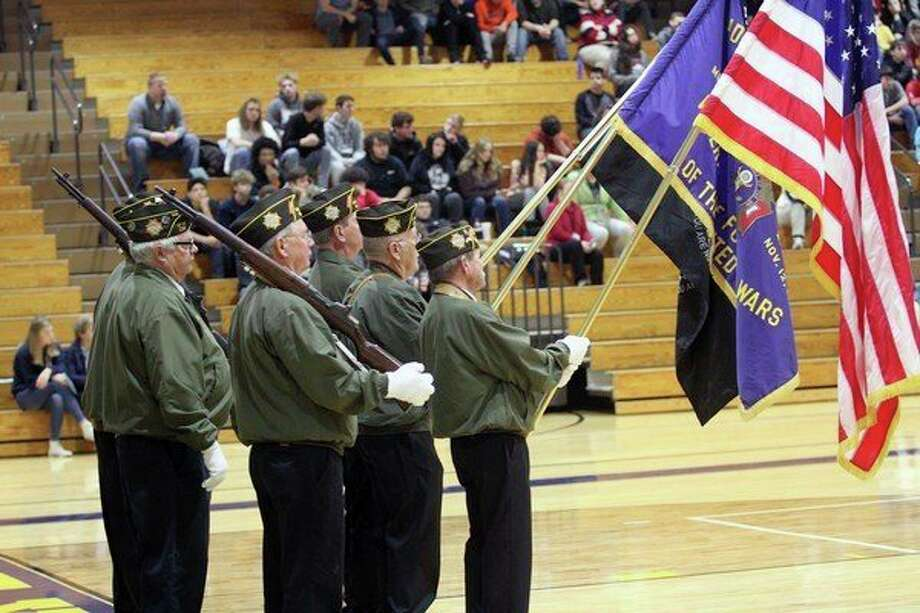 Local veterans display our nation's colors during an assembly at Bad Axe High School Monday in honor of Veterans Day. Several local school districts held events late last week and Monday recognizing our veterans. For more photos from the events, see Page 8A. (Eric Rutter/Huron Daily Tribune)