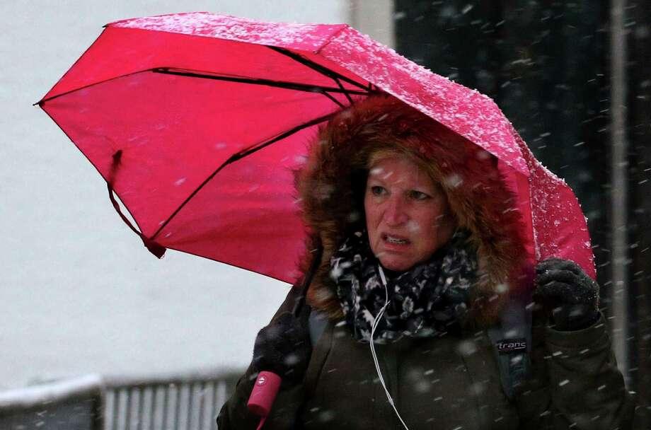 A woman walks with an umbrella during rush hour as snow falls in Chicago, Monday, Nov. 11, 2019. (Antonio Perez/Chicago Tribune via AP) Photo: Antonio Perez / Antonio Perez/Associated Press / Chicago Tribune