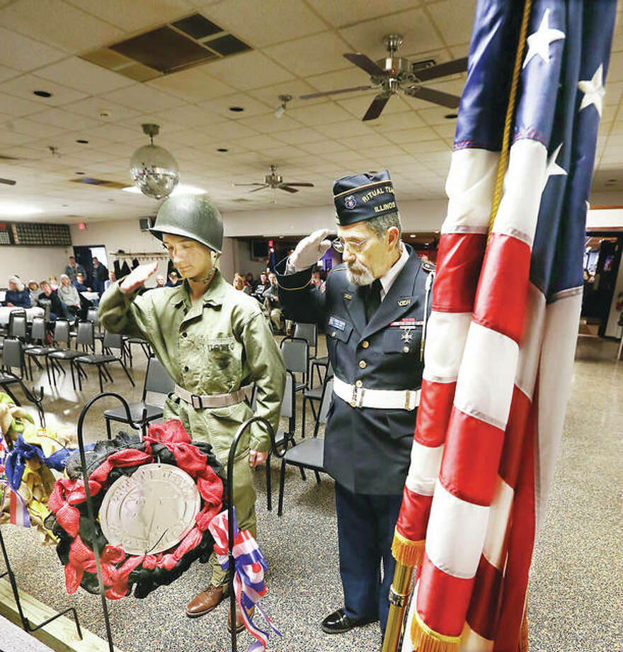 Alton High School Air Force Jr. ROTC member Austin Walsh, left, dressed as a U.S. Marine, salutes the wreath he laid in honor of the U.S. Marine Corps with his real U.S. Marine counterpart, Glen Wilson, right, Monday at the annual Veterans Day observance at the recently renamed Russell E. Dunham Memorial VFW Post 1308 in Alton. Wreaths were laid for four branches of the armed forces and in honor of several other groups, such as the Gold Star Mothers.