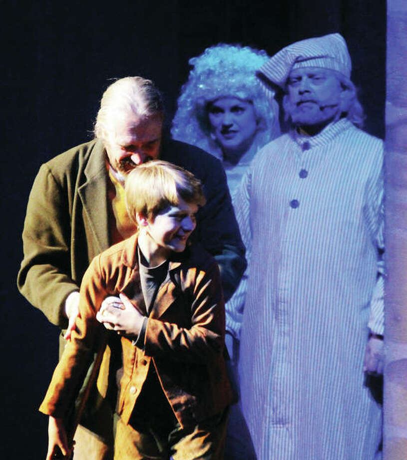 """Ebenezer Scrooge, left, played by Dave Wallace, and the Ghost of Christmas Present, played by his wife, Rachel Wallace, watch Bob Cratchit, played by Tom Johnson, and Tiny Tim, played by Kashton Hansen, during a production of """"A Dickens' Christmas Carol"""" at Silver Dollar City in Branson. The 1880s-themed amusement park started its """"An Old Time Christmas"""" season Nov. 2. """"Christmas Carol"""" is the longest-running show at the park and is now in its 17th year."""