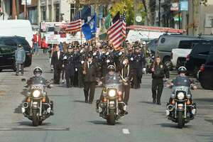 A parade of veterans march down Greenwich Avenue for the Veterans Day ceremony. Monday, Nov. 11, 2019