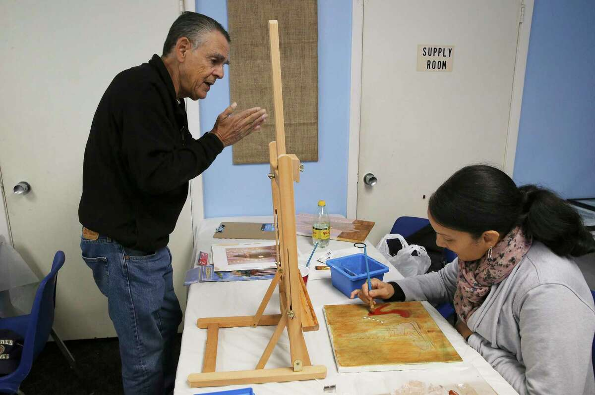 Marine veteran Juvencio Garcia (left) chats with Grace Burmudez, who served in the Army, as she works on a painting during a veterans' art class.