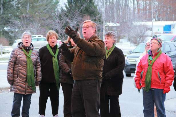 """Crossroads Harmony Sweet Adelines Chorus choral director Jim Whitten leads the choir in song as they sing """"God Bless America."""" Whitten said performing during the Spectrum Health Reed City Hospital Veterans Day Ceremony is one of the choir's favorite performances each year."""