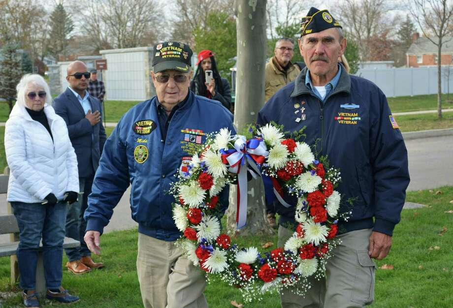 State and local dignitaries joined veterans and their friends and families at the State Veterans Cemetery on Bow Lane in Middletown Monday afternoon to observe Veterans Day. Vietnam veterans Mike Rogalsky, left, and Jerry Augustine of Middletown perform the ceremonial laying of the wreath just before the military salute and playing of taps. Photo: Cassandra Day / Hearst Connecticut Media