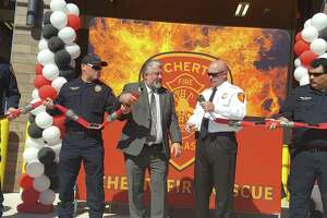 """Schertz Mayor Michael Carpenter and Fire Chief Kade Long (center) take part in the """"hose uncoupling"""" ceremony Saturday — akin to a ribbon-cutting — for the new 2½-bay station. The station is expected to cut response times 40 to 60 percent."""