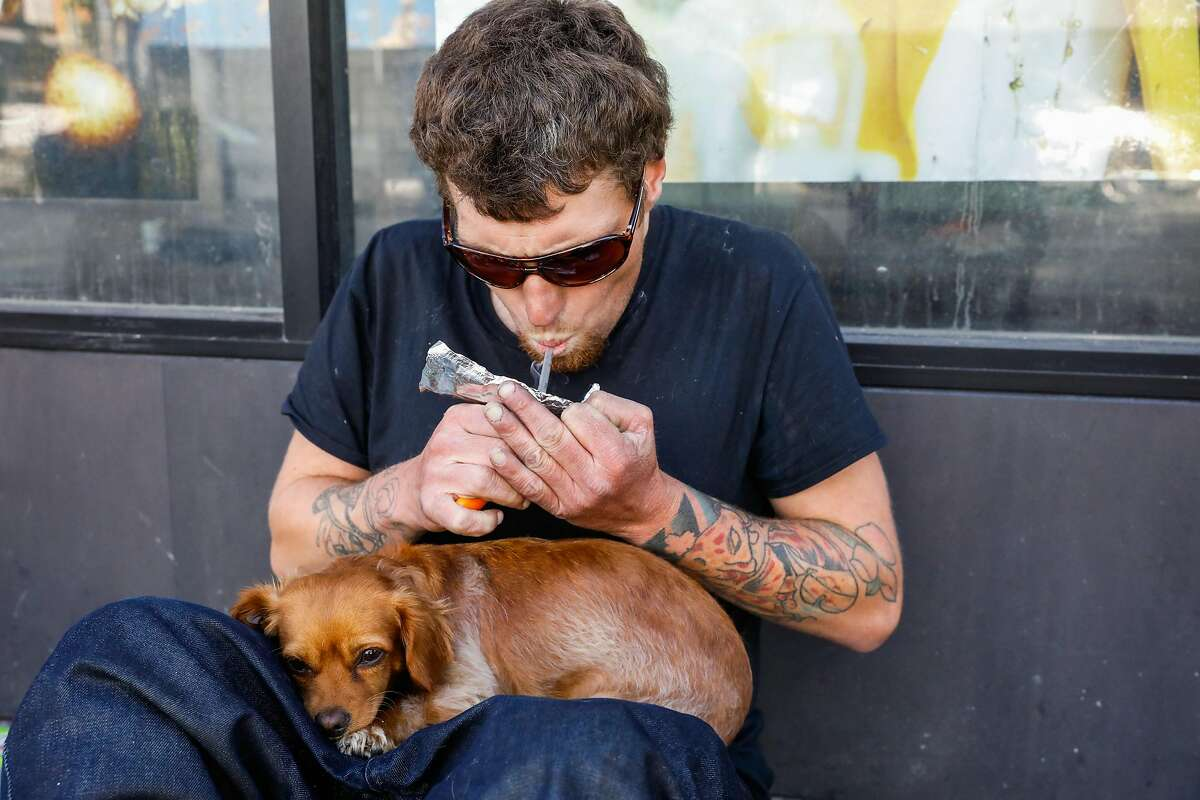 A man smokes fentanyl on Turk Street in S.F. Drug overdose deaths in the city are rising to new highs.