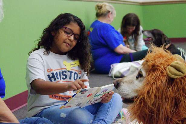 Violet Hicks reads to Casey, a trained therapy dog during the Read to the Dogs program at Helen Hall Library in League City.