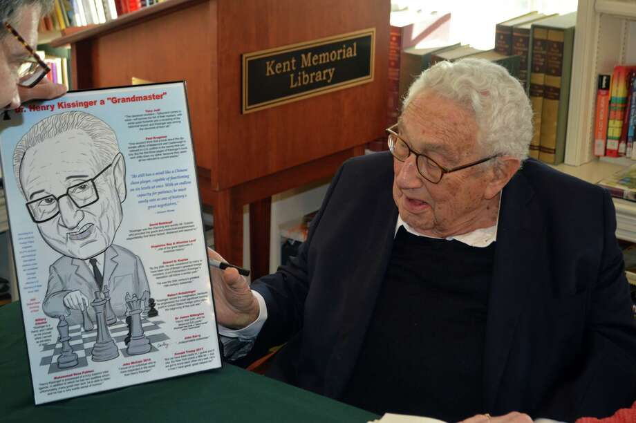 Resident Robert Carley presented a specially-made caricature of Dr. Henry Kissinger during a book-signing on Nov. 9 at the Kent Memorial Library. Photo: Robert Carley / Contributed Photo /
