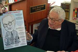 Resident Robert Carley presented a specially-made caricature of Dr. Henry Kissinger during a book-signing on Nov. 9 at the Kent Memorial Library.