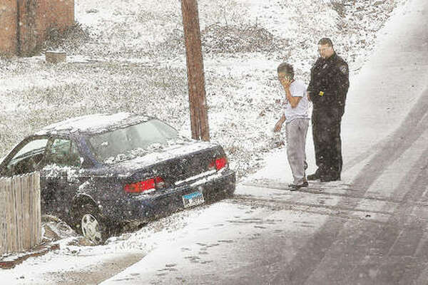 The Riverbend area received its first snowstorm of the season Monday and, with bitter winds and dropping temperatures, it was not pleasant to be out in. Here, Alton Police check on the driver of a car who was uninjured Monday after sliding off an icy Holman Street near College Avenue in Alton.
