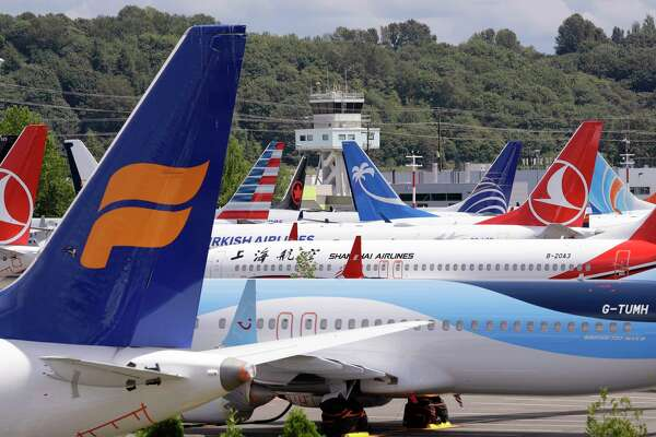 FILE - In this June 27, 2019, file photo, dozens of grounded Boeing 737 MAX airplanes crowd a parking area adjacent to Boeing Field in Seattle. Boeing hopes to resume deliveries of its 737 Max jet to airlines in December and win regulatory approval to restart commercial service with the plane in January. Boeing shares rose in midday trading Monday, Nov. 11. (AP Photo/Elaine Thompson, File)