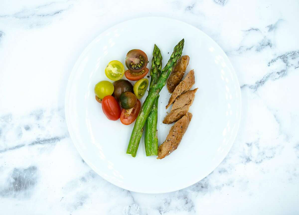 Air-based chicken is served with asparagus and tomatoes. Bay Area company Air Protein makes the meat alternative out of microbes and elements in the air.
