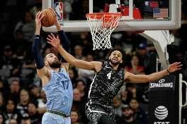 Memphis Grizzlies center Jonas Valanciunas (17) grabs a rebound over San Antonio Spurs guard Derrick White (4) during the first half of an NBA basketball game, in San Antonio, Monday, Nov. 11, 2019. (AP Photo/Eric Gay)