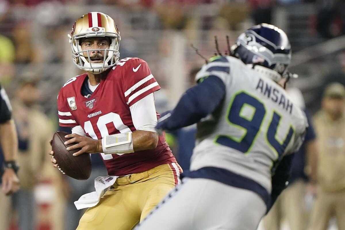 San Francisco 49ers quarterback Jimmy Garoppolo (10) passes against Seattle Seahawks defensive end Ezekiel Ansah (94) during the first half of an NFL football game in Santa Clara, Calif., Monday, Nov. 11, 2019. (AP Photo/Tony Avelar)
