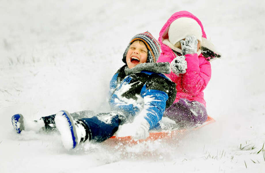 Avery Warner, 8, of Glen Carbon (right) covers her face as she and her brother Luke Warner, 5, sled down the hill at Miner Park in Glen Carbon Monday. They were enjoying this year's first snow with their father Jason Warner. Photo: Thomas Turney | For The Intelligencer