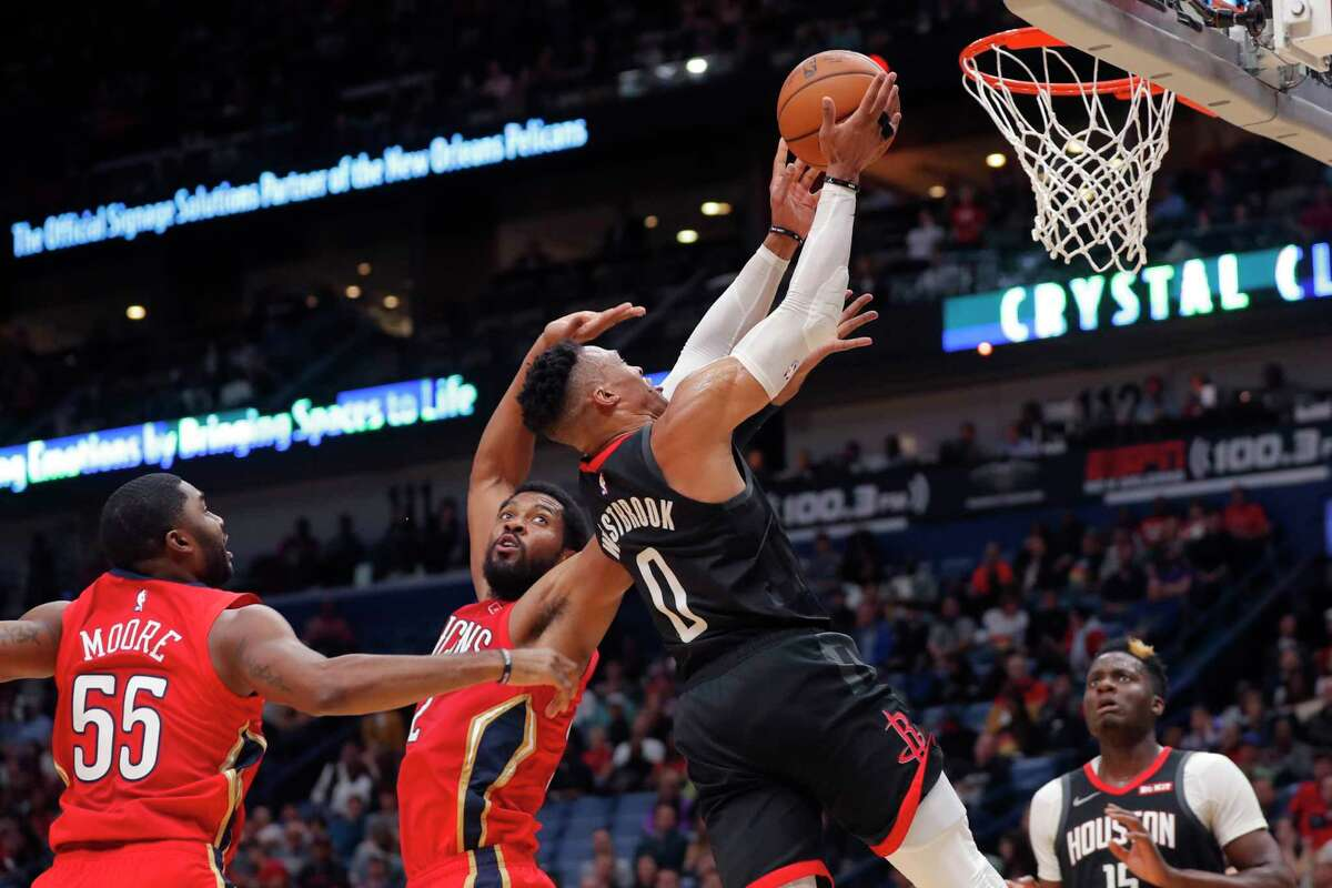 Houston Rockets guard Russell Westbrook (0) is fouled as he drives to the basket against New Orleans Pelicans center Derrick Favors and guard E'Twaun Moore (55) in the first half of an NBA basketball game in New Orleans, Monday, Nov. 11, 2019. (AP Photo/Gerald Herbert)
