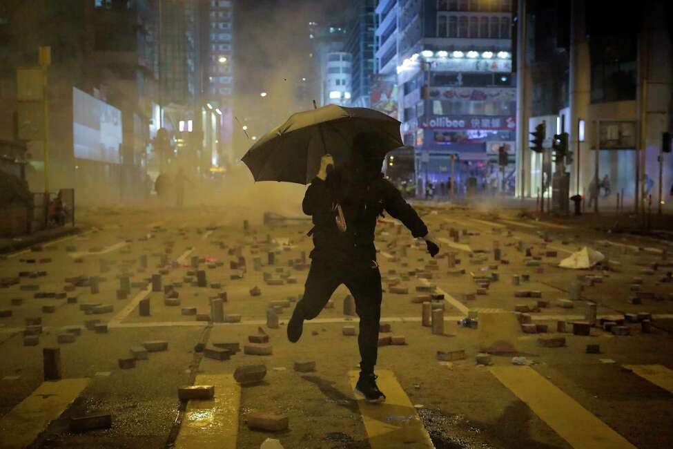 A protester with an umbrella runs away from tear gas fired by riot police on a street scattered with bricks during a protests in Hong Kong, Monday, Nov. 11, 2019. Hong Kong's leader Carrie Lam has pledged to