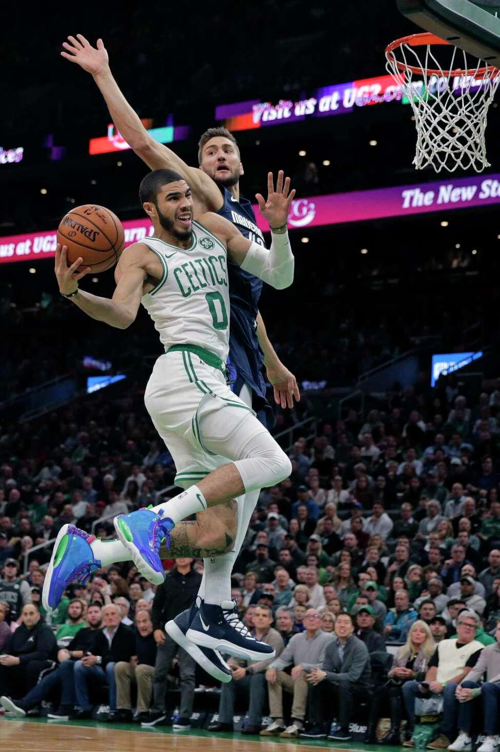 Boston Celtics forward Jayson Tatum (0) drives to the basket against Dallas Mavericks center Maxi Kleber, rear, during the first quarter of an NBA basketball game in Boston, Monday, Nov. 11, 2019. (AP Photo/Charles Krupa)
