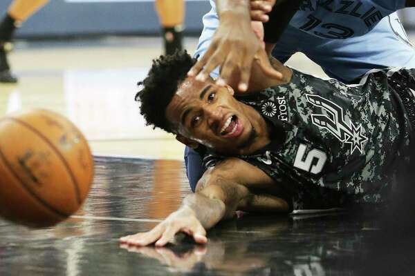 Dejounte Murray loses the ball in the lane with pressure from Jaren Jackson as the Spurs host the Grizzlies on the night of the Tony Parker jersey retirement ceremony at the AT&T Center on Nov. 11, 2019.