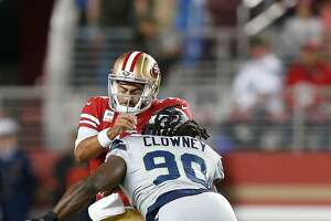 SANTA CLARA, CALIFORNIA - NOVEMBER 11: Quarterback Jimmy Garoppolo #10 of the San Francisco 49ers is tackled by Jadeveon Clowney #90 of the Seattle Seahawks in the first quarter at Levi's Stadium on November 11, 2019 in Santa Clara, California. (Photo by Lachlan Cunningham/Getty Images)