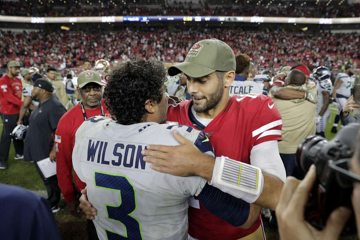 49ers quarterback Jimmy Garappolo (10) congratulates Russell Wilson (3) after the 49ers were defeated 27-24 in overtime by the Seattle Seahawks at Levi's Stadium in Santa Clara, Calif., on Monday, November 11/11/19, 2019.