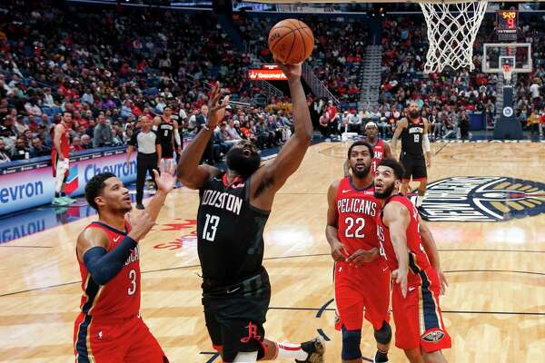 Houston Rockets guard James Harden (13) drives to the basket between New Orleans Pelicans guard Josh Hart (3), center Derrick Favors (22) and guard Kenrich Williams (34) in the second half of an NBA basketball game in New Orleans, Monday, Nov. 11, 2019. The Rockets won 122-116. (AP Photo/Gerald Herbert)