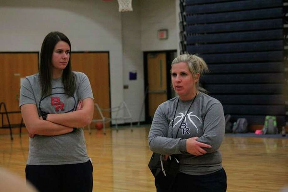 Big Rapids varsity coach Jessica Haist (right) and her assistant Kendra Enszer talk with players after Monday's practice. (Pioneer photo/John Raffel)