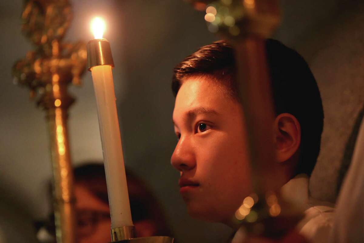 Luke Yonago holds a candle as parishioners gather at St. James Cathedral for a mass in remembrance of the deceased homeless of Seattle, Nov. 7, 2019.